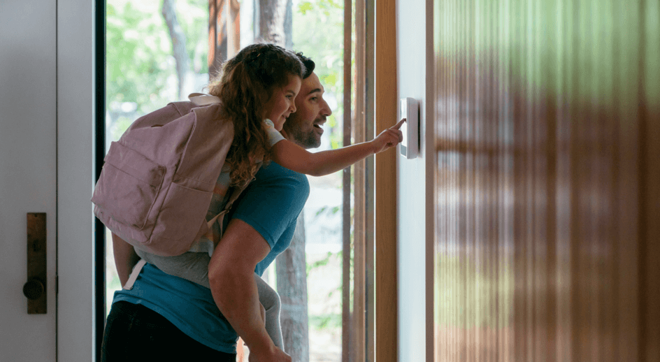 Father and daughter engaging their Vivint Smart Home system before leaving the house