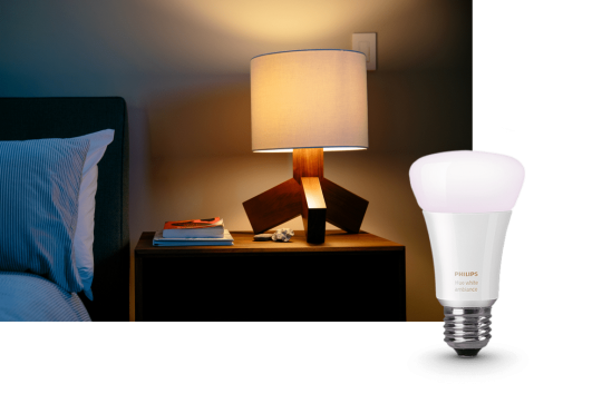 Image with a smart light bulb in the forefront with a lit nightstand lamp in the background.